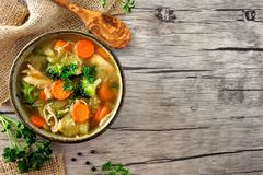 Homemade chicken vegetable soup, above side border on rustic wood. Homemade chicken vegetable soup, above view side border with copy space on a rustic wooden Stock Photo