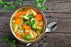 Homemade chicken vegetable soup, top view on rustic wood