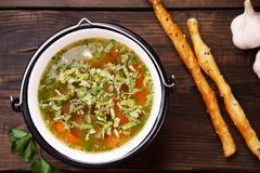 Homemade chicken vegetable soup on wooden table. Homemade chicken vegetable soup on a rustic wooden background and bread sticks, healthy tasty nourishing meal royalty free stock photography