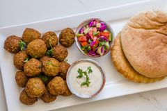 Homemade chickpea Falafel balls in a white plate with salad and tahini sauce pitta bread against white background royalty free stock photos