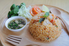 Homemade Chinese fried rice with vegetables, shrimp in spicy tas. Te served on a wooden plate with wooden spoon Royalty Free Stock Photography