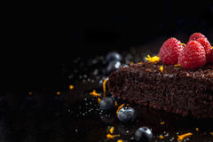 Homemade Chocolate Brownie with raspberries against a dark background Stock Photos