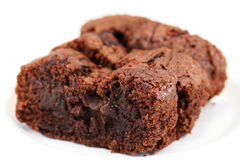 Homemade Chocolate brownies. Three slices of homemade chocolate brownie cake on a white plate against a white background. Shallow depth of field - focus on front stock photo