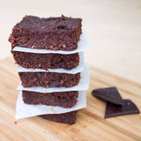 Homemade Chocolate Brownies stacked on beige. Fresh Homemade Vegan Chocolate Brownies stacked separated with parchment paper with two pieces of dark chocolate on Stock Photos