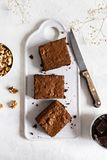 Homemade chocolate brownies with walnuts on white background, top view, copy space royalty free stock images