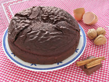 Homemade chocolate cake. Eggshells, nuts and cinnamon over checkered red and white tablecloth Royalty Free Stock Images