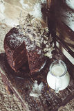 Homemade Chocolate Cake with Coconut Flakes and Dried Flower Decoration Next to a Glass Milk Jug on a Small Vintage Chair Royalty Free Stock Photo
