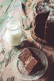 Homemade Chocolate Cake with Coconut Flakes and Dried Flower Decoration Next to a Glass Milk Jug on a Vintage Painted Wood Table Royalty Free Stock Images