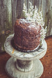 Homemade Chocolate Cake with Coconut Flakes and Dried Flower Decoration on a Small Vintage Wood Reel Stock Photo