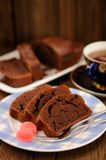 Homemade chocolate cake cut with pink candies and tea in blue cu Royalty Free Stock Photography