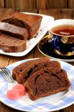 Homemade chocolate cake cut with pink candies and tea in blue cu Stock Photos