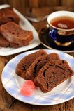 Homemade chocolate cake cut with pink candies and tea in blue cu Stock Image