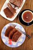 Homemade chocolate cake cut with pink candies and tea in blue cu Stock Images