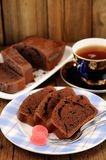 Homemade chocolate cake cut with pink candies and tea Stock Photo