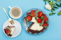 Homemade chocolate cake decorated with fresh strawberries, cup o royalty free stock images
