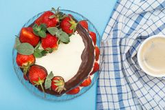 Homemade chocolate cake decorated with fresh strawberries on glass plate and cup of coffee with kitchen napkin. Homemade chocolate cake decorated with fresh stock photo
