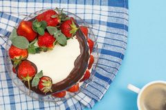 Homemade chocolate cake decorated with fresh strawberries on glass plate with kitchen napkin and cup of coffee. Homemade chocolate cake decorated with fresh royalty free stock photography