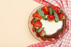 Homemade chocolate cake decorated with fresh strawberries on glass plate with kitchen napkin. Homemade chocolate cake decorated with fresh strawberries and royalty free stock photography