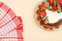 Homemade chocolate cake decorated with fresh strawberries on glass plate with kitchen napkin. Homemade chocolate cake decorated with fresh strawberries and royalty free stock images