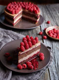 Homemade chocolate cake mousse cheesecake with fresh raspberries on the rustic wooden table. Stock Photos