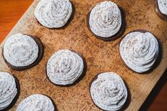 Homemade chocolate cakes with egg white cream and jam on a wooden board stock photography
