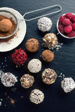 Homemade chocolate candy balls. Homemade chocolate and nuts candy balls with cocoa powder, coconut, berries and chopped hazelnuts on black stone background, top Stock Photos