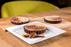 Homemade chocolate chili tart - chocolate cream, hazelnut Chantilly, chili ganache, cocoa biscuits. stock images