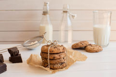 Homemade chocolate chip cookies with bottels of milk, rustic white wooden background. Royalty Free Stock Photography