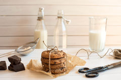 Homemade chocolate chip cookies with bottels of milk, rustic white wooden background. Stock Image