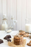 Homemade chocolate chip cookies with bottels of milk, rustic white wooden background. Royalty Free Stock Images