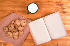 Homemade chocolate chip cookies, milk cup and open book Royalty Free Stock Photo