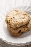 Homemade chocolate chip oatmeal cookies stacked. On two white antique plates Stock Image