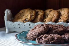 Homemade chocolate, choc chip cookies. Close up of homemade chocolate, choc chip cookies on a plate with oatmeal cookies in the background royalty free stock image