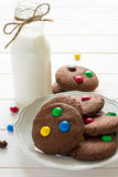 Homemade chocolate cookies decorated with colored candy drops and bottle of milk Stock Image