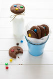 Homemade chocolate cookies decorated with colored candy drops and bottle of milk Royalty Free Stock Photos