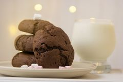 Homemade chocolate cookies and milk. Festive, Christmas background with lights. Homemade chocolate cookies and milk on light background royalty free stock photos