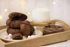 Homemade chocolate cookies and milk. Festive, Christmas background with lights. Homemade chocolate cookies and milk on light background stock photo