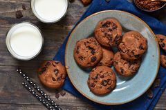 Homemade chocolate cookies in a plate with milk on a wood background.