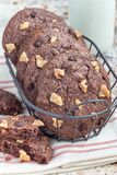 Homemade chocolate cookies with walnuts and chocolate chips in metal basket, vertical Royalty Free Stock Photo