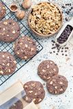 Homemade chocolate cookies with walnuts and chocolate chips on table and cooling rack, vertical, top view Stock Image