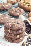 Homemade chocolate cookies with walnuts and chocolate chips on table and cooling rack, vertical Stock Image