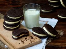 Homemade chocolate cookies with white marshmallow cream and glass of milk on dark background. Selective focus royalty free stock photos