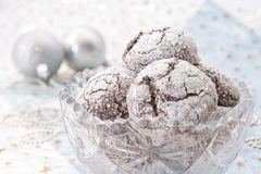 Homemade chocolate cookies wrapped in ribbon. Homemade chocolate cracked cookies in crystal bowl and decorations on blue and white background Stock Photo