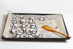 Homemade chocolate crinkle cookies on a baking sheet. On white wooden table Royalty Free Stock Image