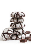 Homemade chocolate crinkles cookies powdered sugar. Stack of homemade chocolate crinkles cookies powdered sugar and pieces of chocolate on white background Royalty Free Stock Photos