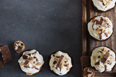 Homemade chocolate  cupcake with nuts and vanilla frosting on wooden board Royalty Free Stock Image