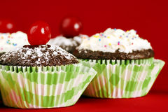 Homemade chocolate cupcakes on red. Delicious chocolate cupcakes topped with powdered sugar and maraschino cherry, other desserts with frosting and candies at Stock Photo