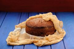 Homemade chocolate fruit christmas cake in cheesecloth on blue t. Able copyspace Royalty Free Stock Photos