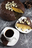 Homemade chocolate-glazed pineapple cake and a cup of coffee with three pieces of chocolate with christmas decorations Stock Image