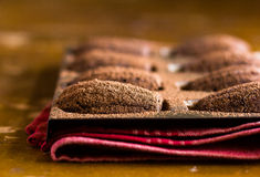 Homemade chocolate madeleines cookies with cinnamon and cocoa powder in a special madeleine mold. On a wooden rustic table, selective focus Stock Photos